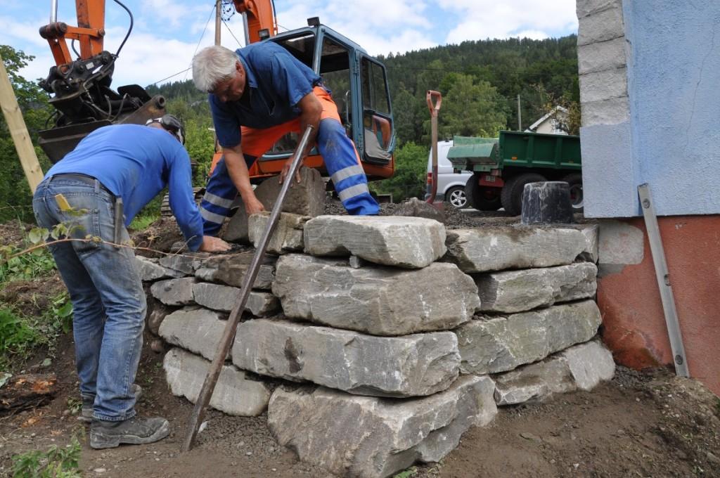 Magne og Ole legg dei siste steinane på plass.